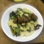 Perogies and Asparagus with vegan alfredo sauce topped with vegan sausage