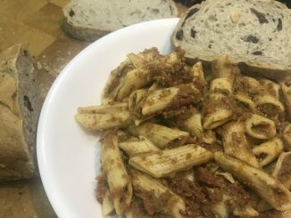A bowl of vegan sausage tomato sauce covered penne pasta